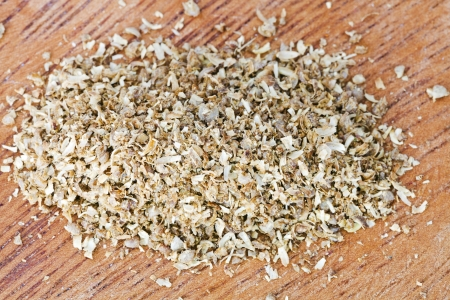 freshly ground dried coriander seeds on wooden board photo