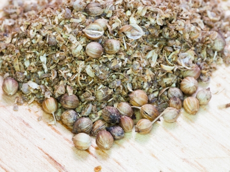 freshly milled coriander and dried coriander seeds on wooden board photo