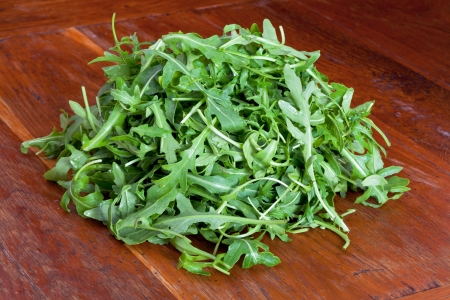 roquette: heap of fresh rucola salad on wooden table