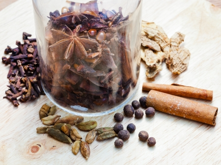 glass bottle and spices for mulled wine on wooden table close up photo