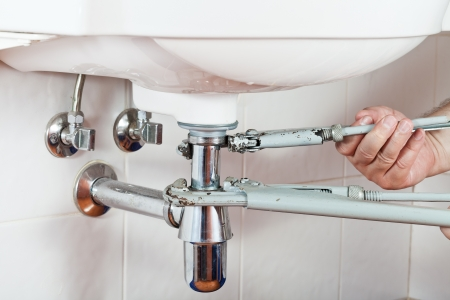 plumber repairing sink drain by pipe-wrenches