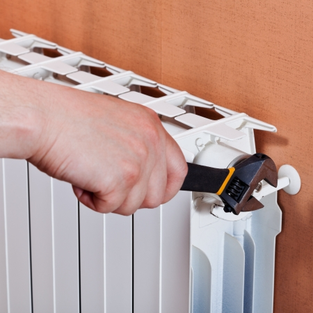 adjusting heating radiator by adjustable wrench photo