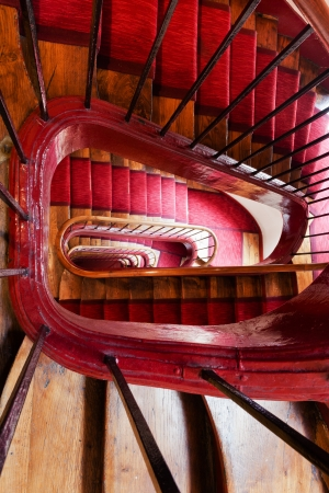 spiral steps with red carpet strip in old house Stock Photo