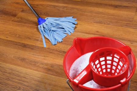 red bucket and mopping of parquet floors photo