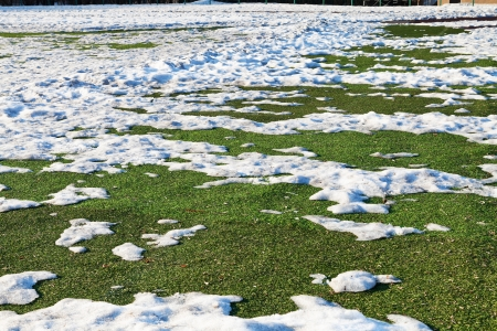 thawing: snow on outdoor soccer field in low season Stock Photo