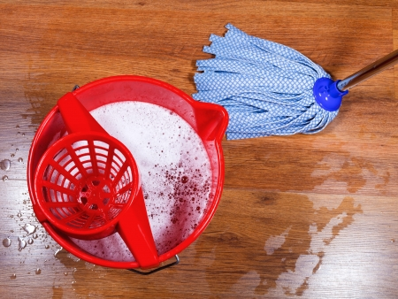 red bucket and mopping of wooden floors photo