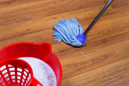 red bucket with water and mopping of laminate floors photo