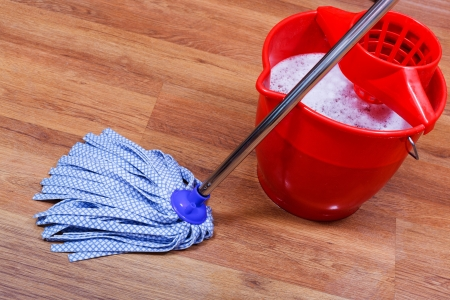 blue textile mop and red bucket on wooden floor Stock Photo