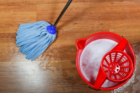 cleaning of wooden floors and red bucket with washing water photo