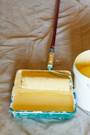 emulsion: plastic paint tray with yellow emulsion paint and painter roller brush Stock Photo