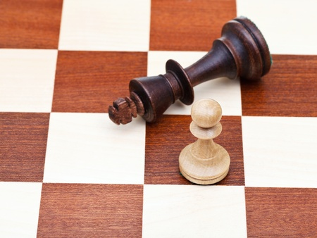 pawn to king: standing and fallen chess king and pawn close up