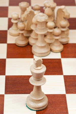 top view of chess pieces against the king close up photo