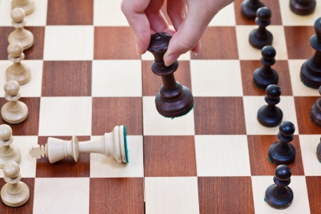 hand with Black King knocks white king on chess board photo
