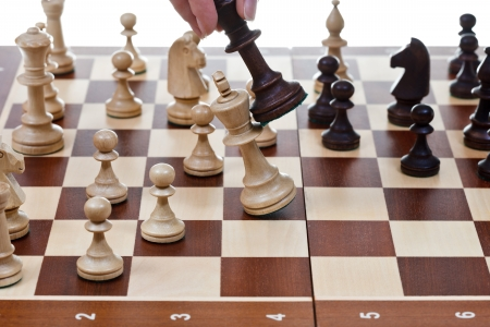 hits: hand with black king hits white king on chessboard in chess game