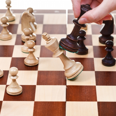 hand with black king overturns white king on chessboard in chess game photo