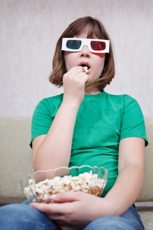 Girl watching TV movies in anaglyph stereo glasses and eating popcorn photo