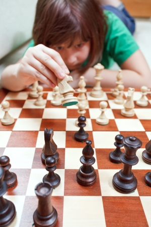 little girl girl moves knight playing chess lying on couch photo