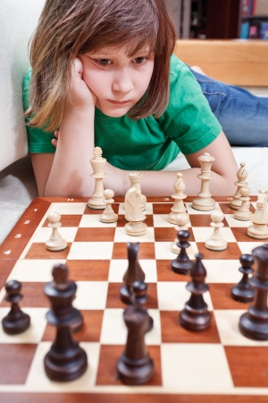 little girl playing chess game lying on couch photo