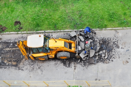 roadmen and tractor remove asphalt from road Stock Photo - 21346932