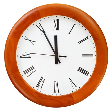 at five minutes to twelve o clock on round dial clock photo
