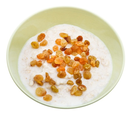 traditional english oat porridge with raisins in ceramic bowl isolated on white background photo