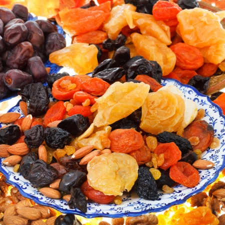background from sweet dried fruits on asian plates photo