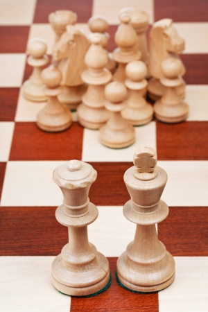 chess figures against the king and queen close up photo