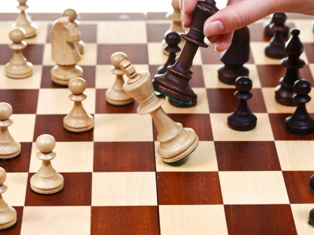 overturn: hand with black king throws white king on chessboard in chess game