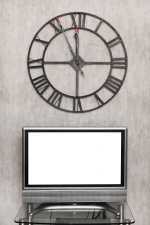 five minutes to midnight on wall clock under blank white screen of TV set photo