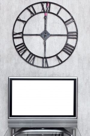twelve o clock on wall clock under blank white screen of TV set photo