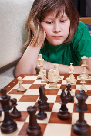 little girl thinking over chess game lying on couch photo