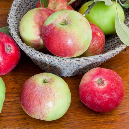 red and green apples in basket on wooden table close up photo