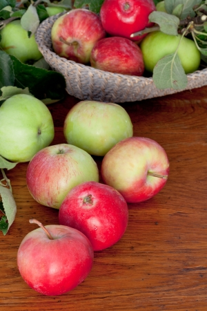 many red and green apples with leaves on wooden table close up photo