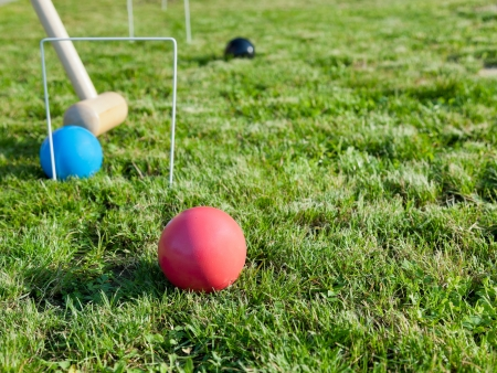 mallet and balls in game of croquet on green lawn in summer day