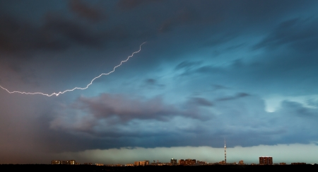 lightning bolt in storm clouds over city in summer evening photo