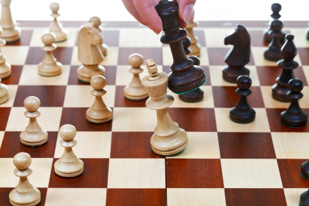 hand with black king beats white king on chessboard in chess game photo