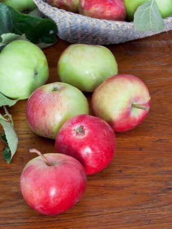 several red and green apples on wooden table close up photo