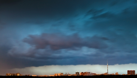 storm clouds over city in summer evening photo