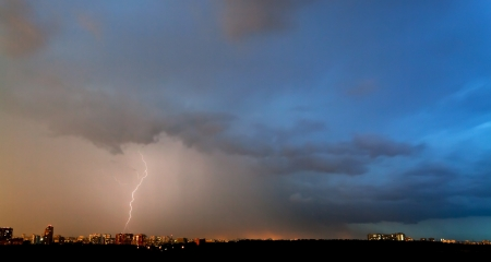 storm and thunderbolt over city in summer evening photo