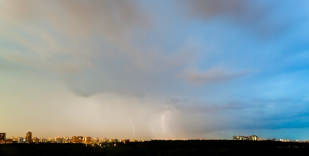 thunderstorm over city in summer evening photo