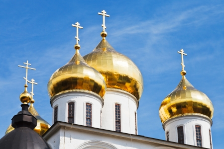 golden cupola of russian church Dormition Cathedral under blue sky in Dmitrov Kremlin, Russia photo