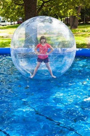 meisje in het water bal in het open zwembad Stockfoto