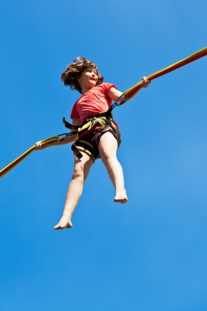 girl on bungee cord with blue sky background photo