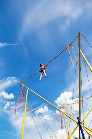 girl jumps on bungee cord device in summer day photo
