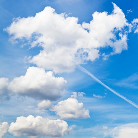 cloudscape with white fluffy clouds and trace of plane in blue sky in summer day photo
