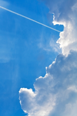 cloudscape with trace of air plane in blue sky in summer evening photo