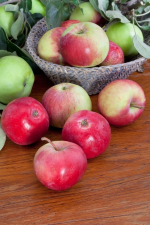 fresh summer apples with green leaves in basket on wooden table photo