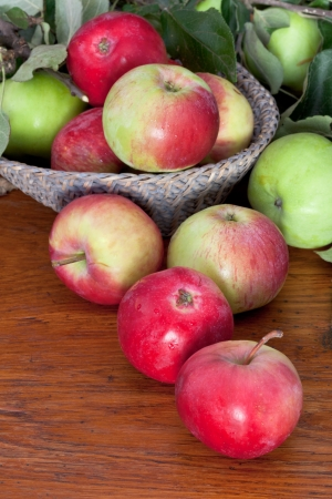 fresh apples with green leaves in basket on wooden table close up photo