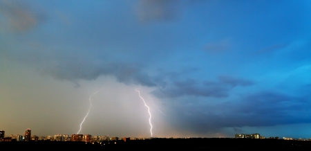two lightning strikes over city in summer evening photo