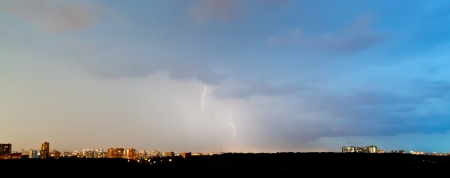 panoramic view of thunderbolts in dark blue sky over city in summer evening photo